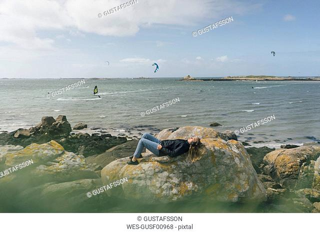 France, Brittany, Landeda, young woman wearing headphones lying on rock at the coast