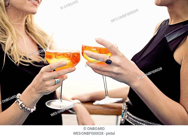 Two women toasting with aperitive, close-up