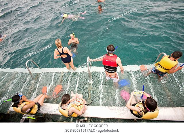 Tourists snorkelling from a dive and snorkel platform anchored to the Great Barrier Reef off Cairns in Queensland, Australia