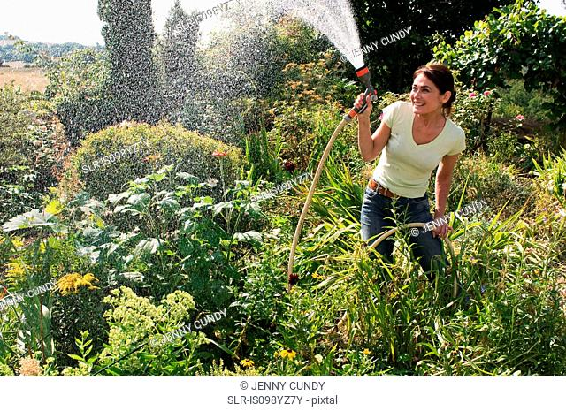 Woman spraying garden with hosepipe