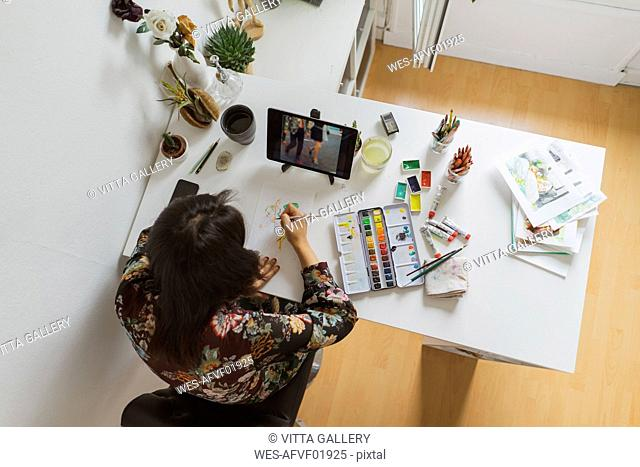 Illustrator painting at work desk in an atelier using digital tablet, top view