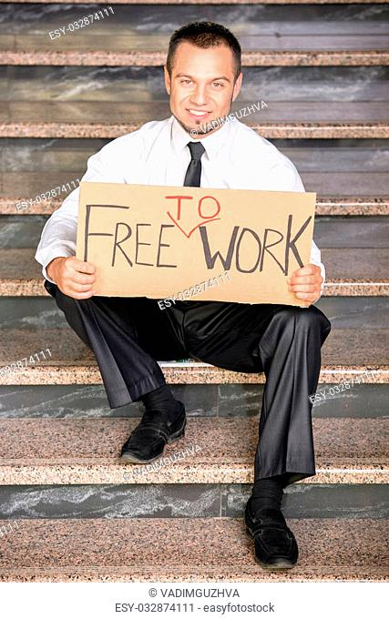 Fired businessman is searching for a job, sitting on the stairs