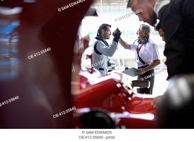 Manager and formula one race car driver high-fiving in repair garage