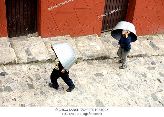 Men carry large metal pans for sale or barter in the Sunday market in Cuetzalan del Progreso, Mexico. Cuetzalan is a small picturesque market town nestled in...