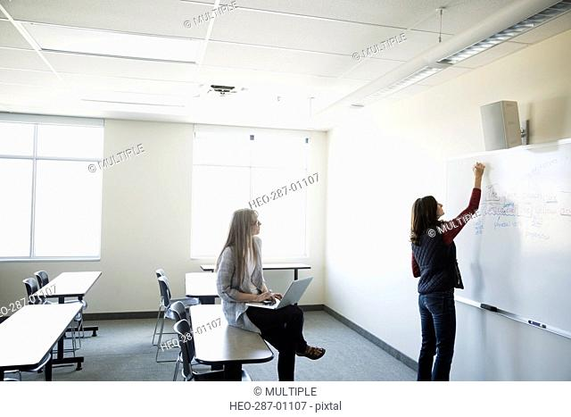 Professor with laptop watching student at whiteboard in classroom