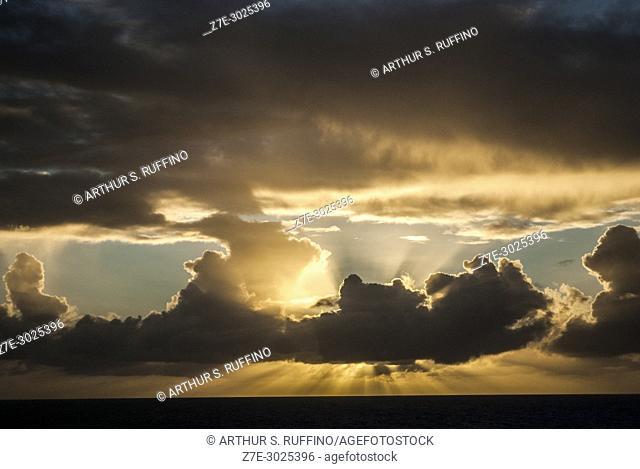 Cloud formations at sunset. Descending sun paints the sky