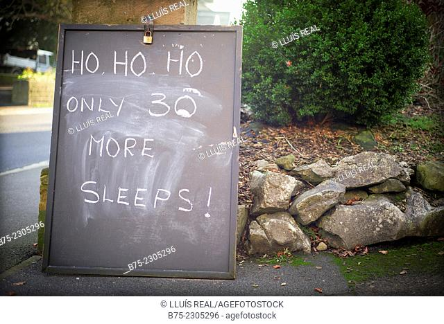 Slate supported by a dry stone wall, on the street and with handwritten text: Ho, Ho, Ho, only 30 more sleeps! When 30 days left for Christmas