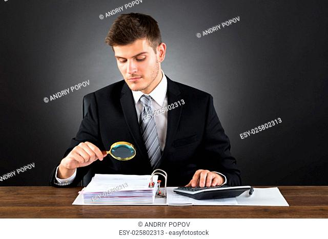 Young Businessman Scrutinizing Invoice With Magnifying Glass