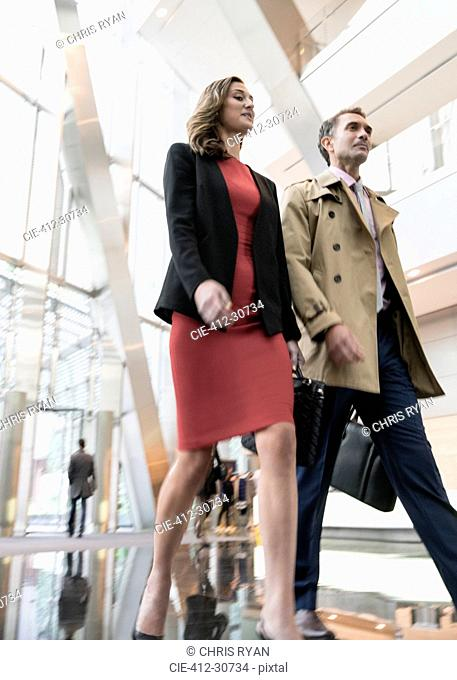 Corporate businessman and businesswoman walking in modern office lobby