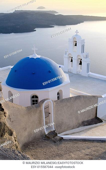 view of a typical church in White and Blue and the caldera at sunset on the island of Santorini Greece