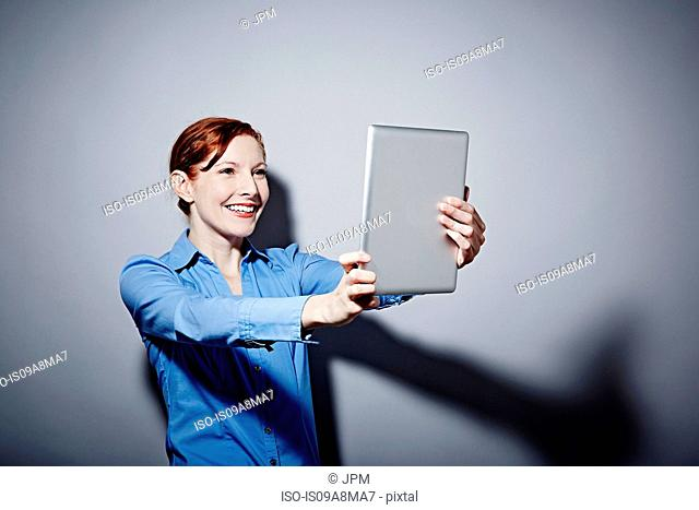 Studio portrait of young woman holding up digital tablet