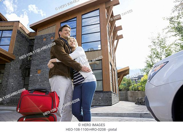 Couple with luggage hugging outside hotel