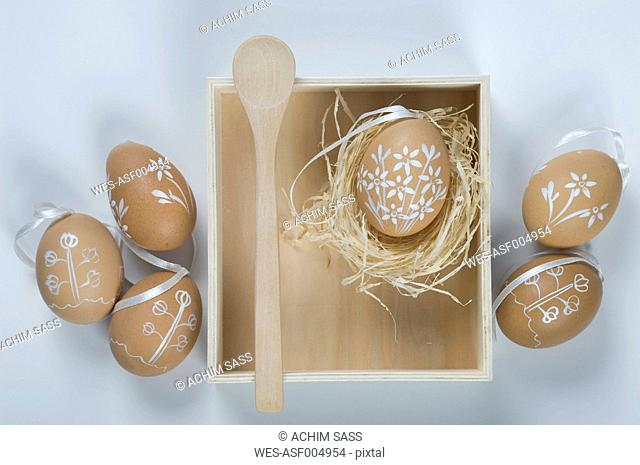 Painted easter eggs in box with straw and wooden spoon