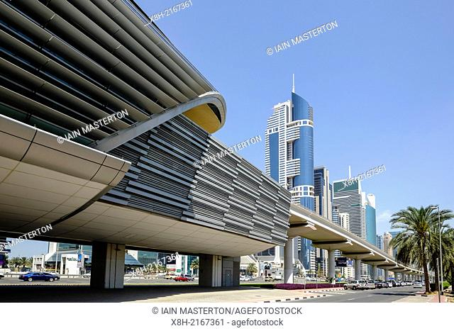 Daytime skyline view along skyscrapers and elevated metro station and viaduct on Sheikh Zayed Road in Dubai United Arab Emirates