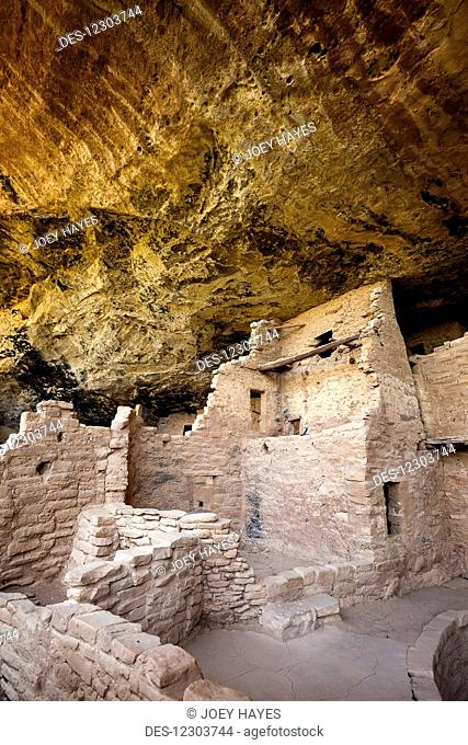 Inside the Spruce Tree House cliff dwellings at Mesa Verde National Park with ancient ruins under a sweeping rock overhang; Colorado, United States of America