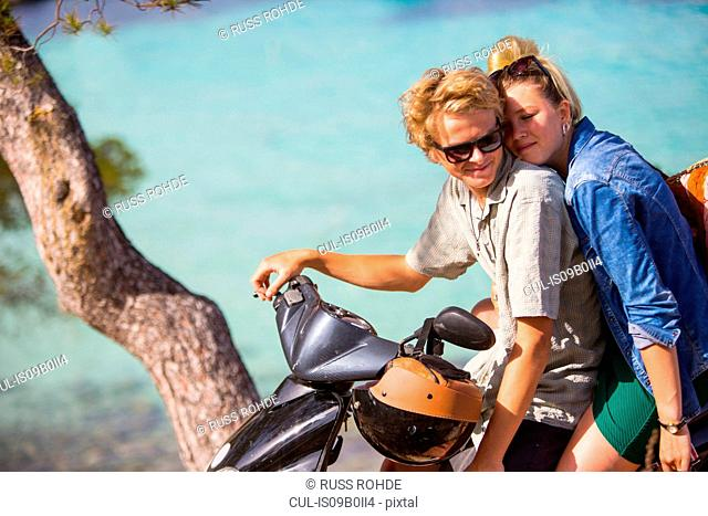Romantic young couple sitting on moped at coast, Majorca, Spain