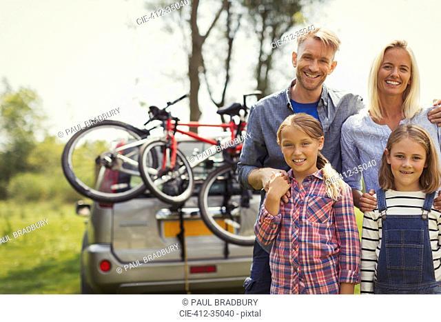 Portrait smiling family near car with mountain bikes