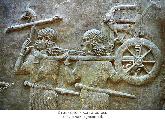 Stone relief sculptured panel of soldiers carrying a chariot . Facade L. Inv AO 19884 from Dur Sharrukin the palace of Assyrian king Sargon II at Khorsabad