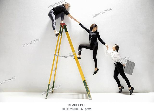 Businesswomen holding hands, helping lift each other on ladder
