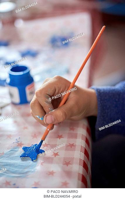 Hispanic boy painting stars at table