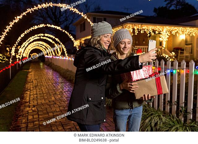 Caucasian mother and daughter holding Christmas gifts posing for selfie