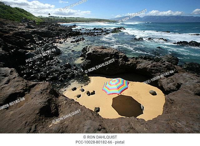 Brightly colored beach umbrella in a sandy circle surrounded by lava rock next to the ocean