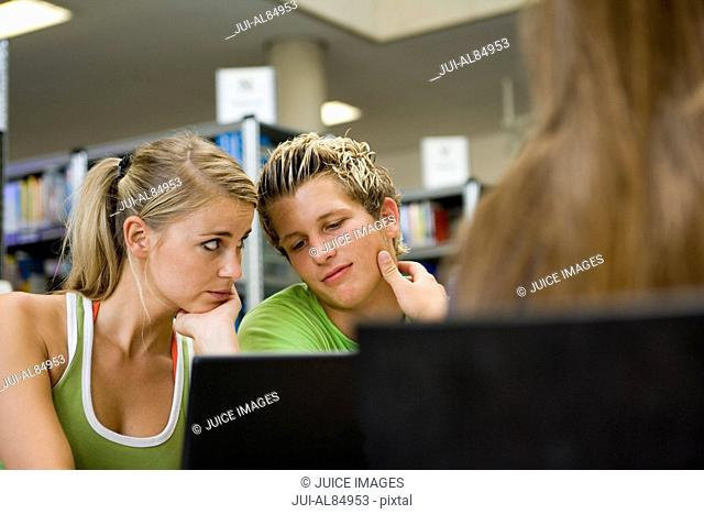 Teenage couple studying with laptop in library
