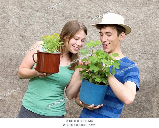Young couple with two potted plants, Tagetes tenuifolia and Ribes