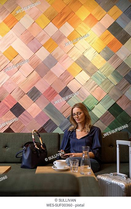 Portrait of businesswoman with baggage in a cafe looking at cell phone