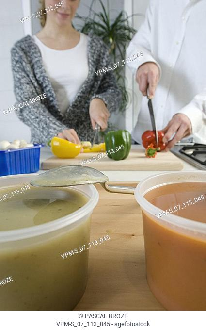 Close-up of two cups of soup in the kitchen with a couple cutting peppers behind