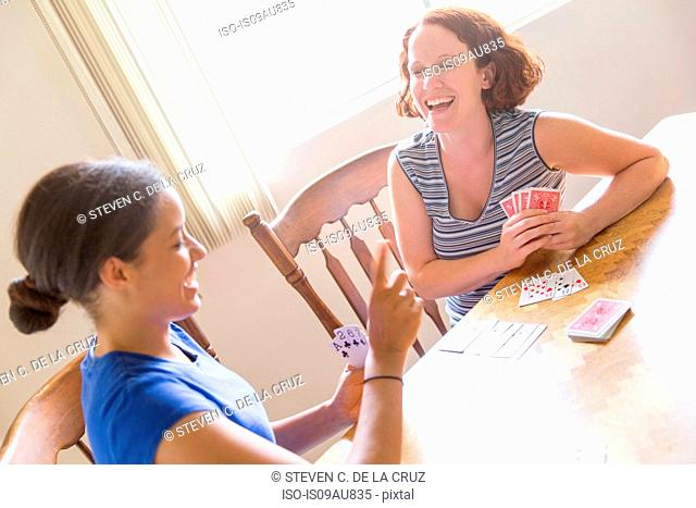 High angled view of young women sitting at dining table playing cards smiling