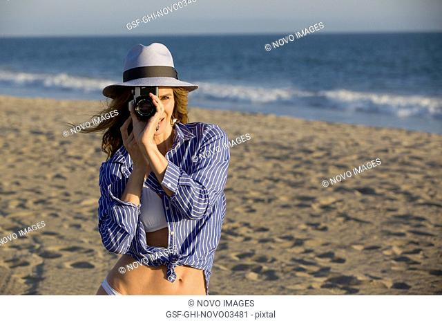 Half-Length Portrait of Mid-Adult Woman Looking Through Camera Lens at Beach