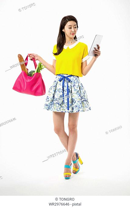 Young smiling woman in casual clothes posing with tablet and shopping bag