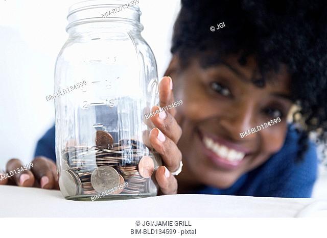 Black woman saving coins in jar
