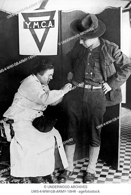 London, England: c. 1917.A soldier gets some last minute repairs made to his uniform by a woman at the YMCA in London