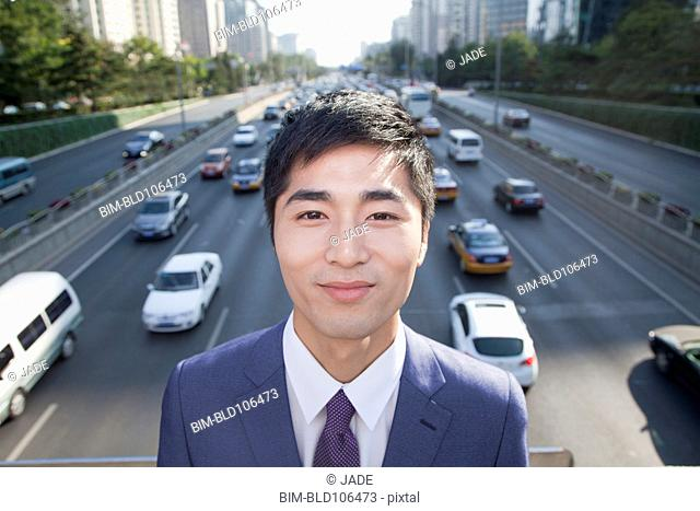 Chinese businessman standing on busy overpass