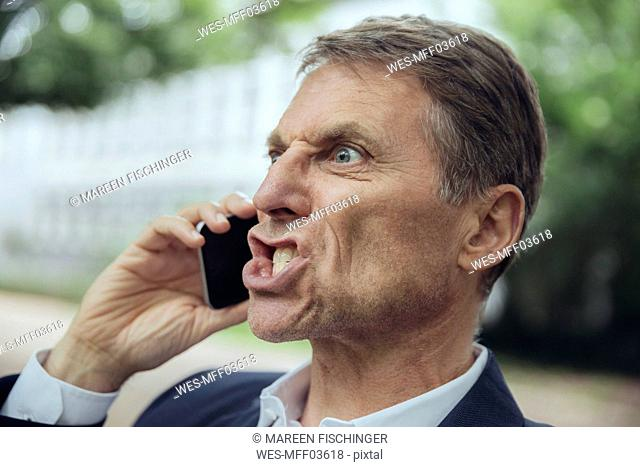 Portrait of angry mature businessman outdoors on the phone
