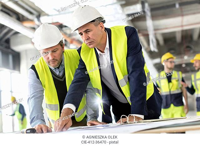 Male engineers viewing blueprints at construction site