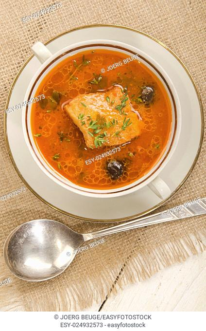 mediterranean fish soup with tomato, onion and black olive served in a bowl
