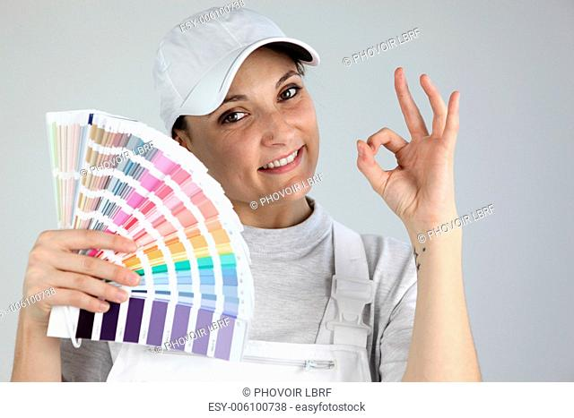 Painter giving the a-ok sign and holding a palette of colour samples