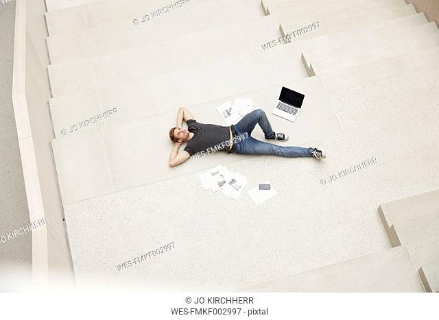 Young man lying on staircase with laptop and papers