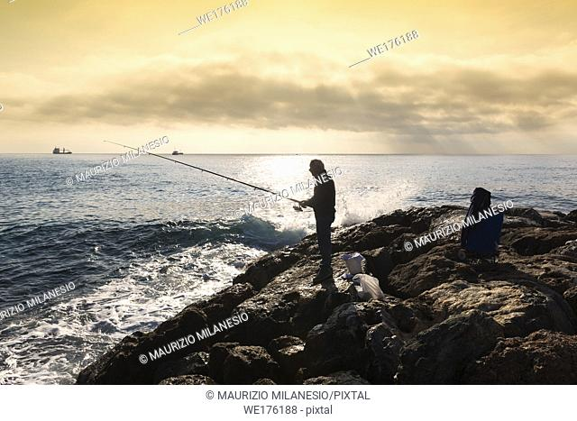 Savona, Italy. A fisherman standing with the fishing rod in his hand, he is on the rocks at sunset, near him buckets and equipment in bags