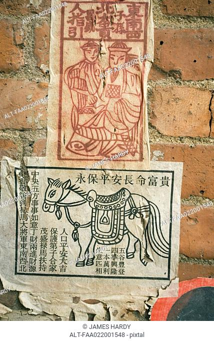Flyers pasted to wall with Chinese script