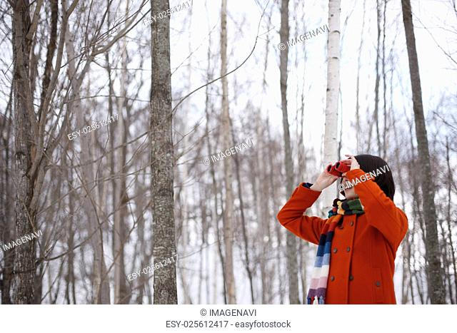 A woman peering through binoculars