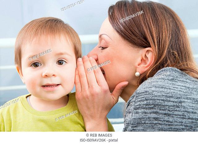 Mother whispering into son's ear