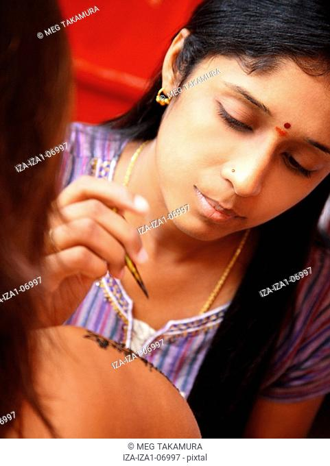 Close-up of a young woman applying henna tattoo on another woman's arm
