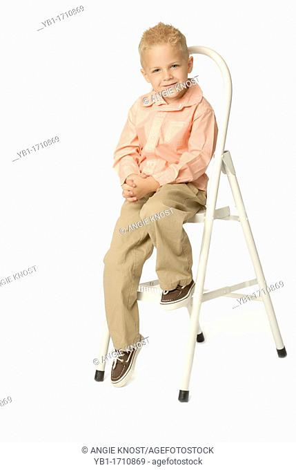 Cute, blond five year old boy sitting on a stepladder  Caucasian ethnicity  He is wearing khaki pants and a button-down shirt