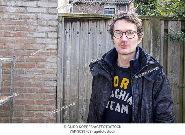 Tilburg, Netherlands. Adult caucasian man at the garden door of his back yard, getting ready to do some household shopping
