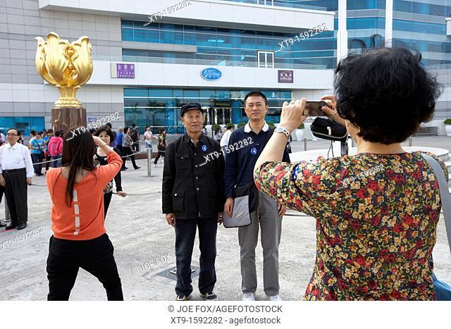 mainland chinese tourists taking photos in golden bauhinia square hong kong island, hksar, china