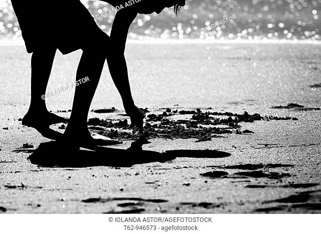 Silhouette of a child drawing on the sand at the beach  Black and white